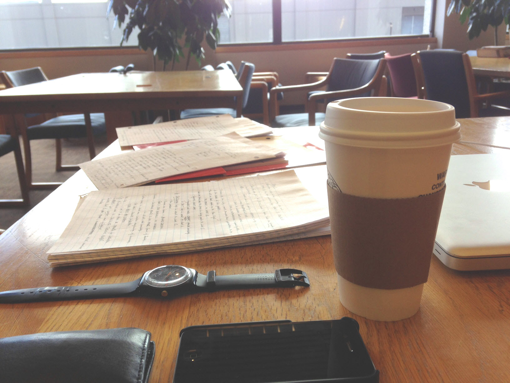 Photo of covered cup of coffee with student's study materials
